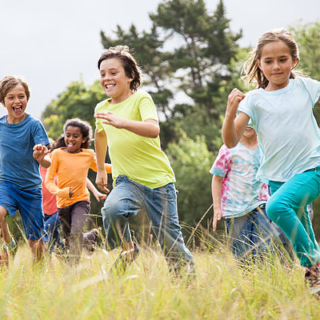 Children, aged 9-10, running together in a park